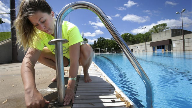 Lifeguard Emily Batley installs and secures a ladder at Erb Park Pool in Appleton.