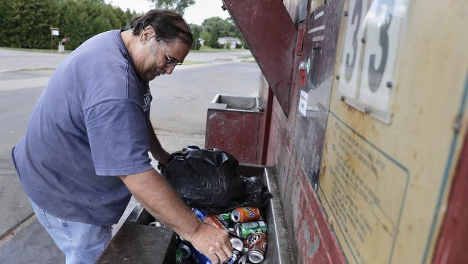 Dave Arndt of Menasha recycles aluminum cans at the self service Golden Goat connected to Appleton Aluminum Recycling.