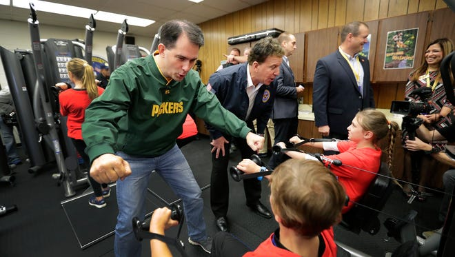 Governor Scott Walker, left, and Jake Seinfeld, chairman of the National Foundation for Governors' Fitness Councils, encourage students Nathan Schmidt, bottom left, and Mandy Frase as they try new fitness equipment in the new Don't Quit Fitness Center on Friday, October 7, 2016, at Badger Elementary School in Grand Chute, Wisconsin. The school received the $100,000 center after applying through the National Foundation For Governors' Fitness Councils.
