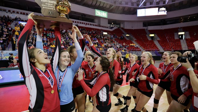 Newman Catholic players celebrate with the Division 4 championship trophy after the Fighting Cardinals defeated Clayton in the Division 4 championship match at the WIAA state girls volleyball tournament at the Resch Center on Saturday, November 5, 2016, in Ashwaubenon, Wis. Newman Catholic won the championship with a 3-0 victory.