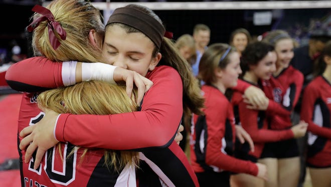 Newman Catholic's Lauren Fech, right, hugs Mariah Whalen after Newman Catholic defeated Clayton in the Division 4 championship match at the WIAA state girls volleyball tournament at the Resch Center last week. Both Fech and Whalen signed a national letter of intent Wednesday morning.