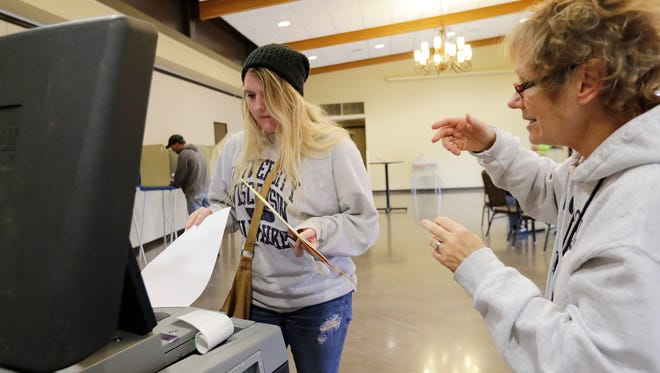 Polling site worker Gail Rudnick, right, instructs first-time voter Tia Beauleau how to insert her ballot into the machine at the Green Bay Botanical Garden on Nov. 8 in Green Bay.