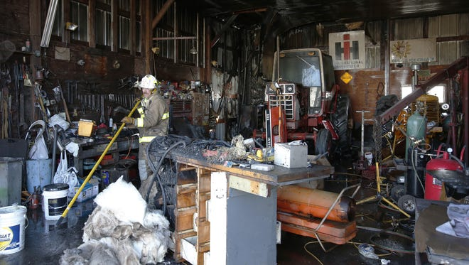 Kellnersville firefighters remove debris from a machine shed after a propane furnace started a fire at Cloverdale Farms Dec. 20 in Whitelaw.