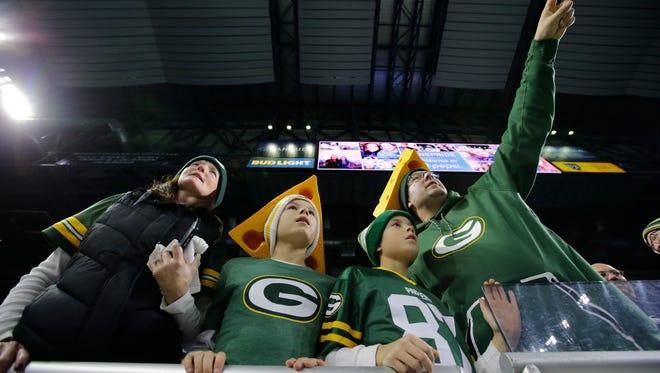 Quentin Greer, far right, of Ontario, Canada, points out Green Bay Packers' quarterback Aaron Rodgers to his wife Kelly, far left, and sons Cameron, 11, and Brody, 9, as players warm up for their game against the Detroit Lions. Sunday, January 1, 2017, at Ford Field in Detroit, Mich.