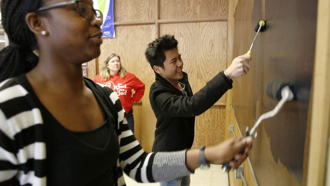 "Lincoln senior Athea Watson and junior Marshall Thao put the first coat of chalkboard paint on their interactive ""I Have a Dream"" wall as Rachael George supervises Thursday, Jan. 12, in Manitowoc."