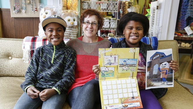 Tammy poses with her son Quirt and daughter Olivia as Olivia shows off the published picture and the signed Scoopie photograph she got after winning a national Culver's coloring contest.