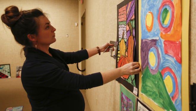 Andrea Ortega, an art teacher at Franklin, hangs her students' artwork for the MPSD art show Thursday, Feb. 22, in Manitowoc.