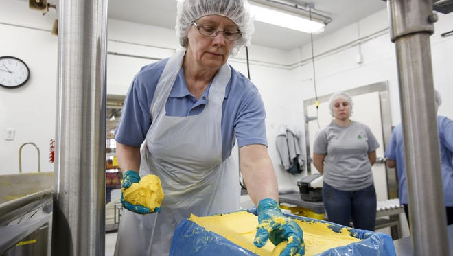 Joan Reindl, a 32-year Pine River employee, packs freshly made butter for shipping Tuesday, Feb. 23, in Manitowoc.