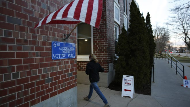 A voter rushes inside to cast her ballot in Manitowoc. Polls are open until 8 p.m. today.