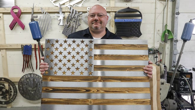 Shane Henderson poses with one of the popular American flag designs in his shop April 27 in Manitowoc. Flags like this are donated to heroes whose stories are submitted and selected as a part of the Flags for Fortitude program Henderson created to celebrate those who show courage in the face of adversity.