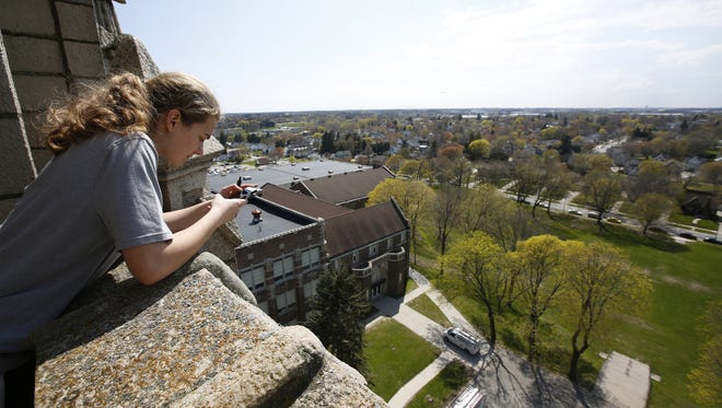 Lincoln senior Carol Neff photographs the view from the top of the tower as students toured Lincoln High School's tower Thursday in Manitowoc.