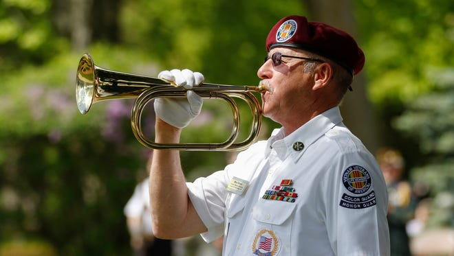 Marv Decker plays taps for the during a Memorial Day ceremony Monday, May. 29, 2017, in Manitowoc, Wis.