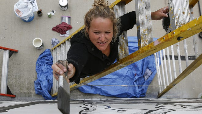 File - Local artist and Silver Lake College professor Erin LaBonte works on the 10th Street mural June 13, 2017, in Manitowoc.