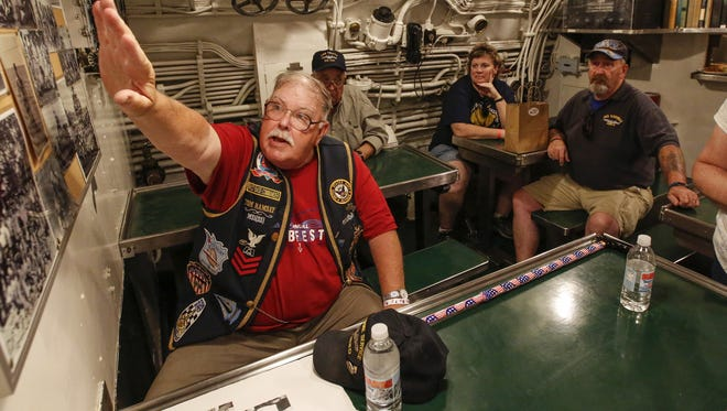 Submarine veteran Tom Ramsay, left, gives people a tour of the mess hall in the USS Cobia on the opening day of Subfest Friday in Manitowoc. Ramsay served in the Navy for 21 years as a head chef.