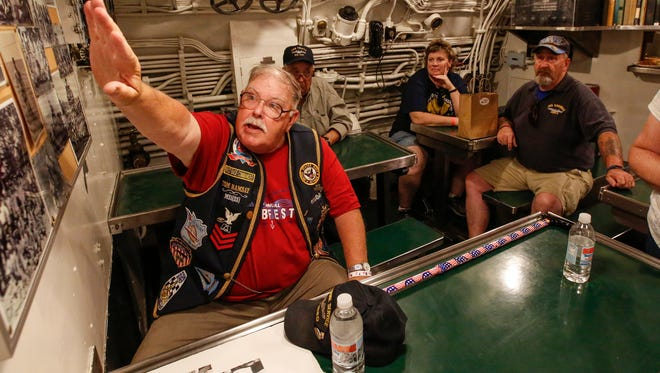 In this July 7, 2017, photo, submarine veteran Tom Ramsay gives people a tour of the mess hall in the USS Cobia on the opening day of Subfest.