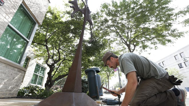 "Sam Spiczka of Sauk Rapids, Minn., anchors his sculpture ""Athena"" along College Avenue in Appleton."