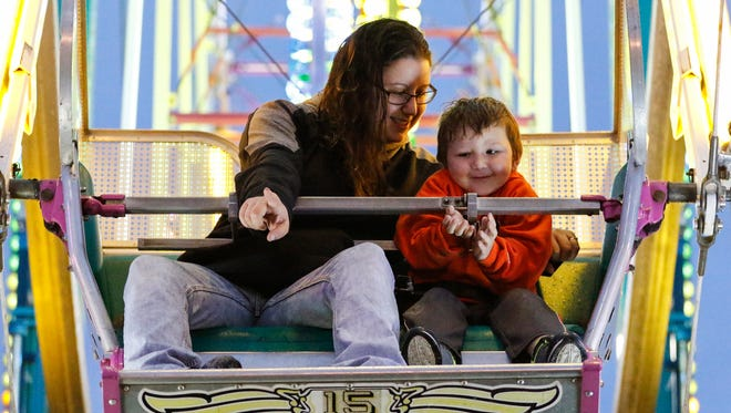 Jennifer Anderson points out family to son Ryder Anderson, 3, while on the Ferris Wheel at the Manitowoc County Fair Saturday, Aug. 26, 2017, in Manitowoc, Wis. Josh Clark/USA TODAY NETWORK-Wisconsin