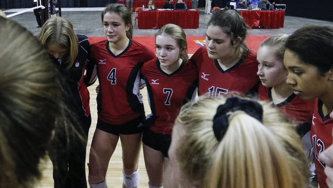Newman Catholic players listens to their coach after losing to Clayton in five sets in a WIAA Division 4 state semifinal match Friday in Ashwaubenon.