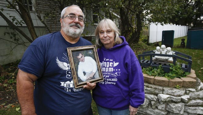 Jeff and Barb Lenzner hold a picture of their son Kurt outside their house Oct. 26 in Manitowoc. Kurt died from a heroin overdose in 2014.