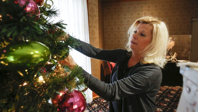 """Paula Feest places ornaments on her display for """"Christmas in the Mansion"""" at the Rahr-West Museum Nov. 16 in Manitowoc. Feest is one of 18 volunteers helping with 12 displays."""