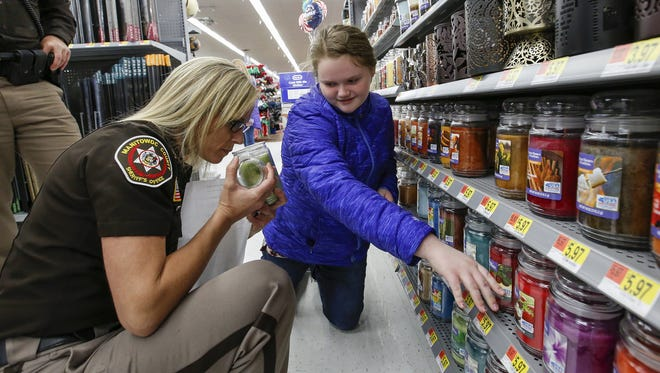 Manitowoc County Sheriff officer Shauna Fruzen helps Olivia, 11, find a gift candle at Walmart during the Shop with a Cop event Dec. 6 in Manitowoc.