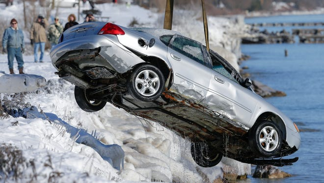 Hi-Way 42 Towing assists the Manitowoc Fire department in pulling out a car from Lake Michigan Thursday, Dec. 14, 2017, in Manitowoc, Wis. High winds and heavy snowfall caused the car to slide off Maritime Drive into Lake Michigan Wednesday morning. Josh Clark/USA TODAY NETWORK-Wisconsin