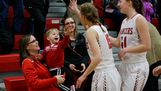 Lacy Behnke, left, holds her son Braxton, 1, as he celebrates with the Lancer girls after they defeated Kohler 57-45 at Manitowoc Lutheran High School Tuesday, Jan. 9, 2018, in Manitowoc, Wis.