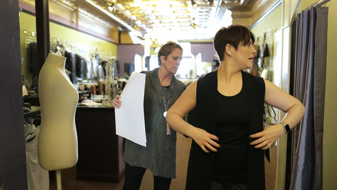 Kara Manuel, left, owner of Lillians of Appleton, assists Rachel Lau of Kaukauna with a fitting. Lillians unveils its expansion Thursday in downtown Appleton.