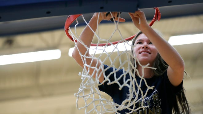 Appleton North's Kari Brekke cuts down the net during a ceremony at the school Tuesday celebrating the Lightning's second consecutive Division 1 state basketball title.