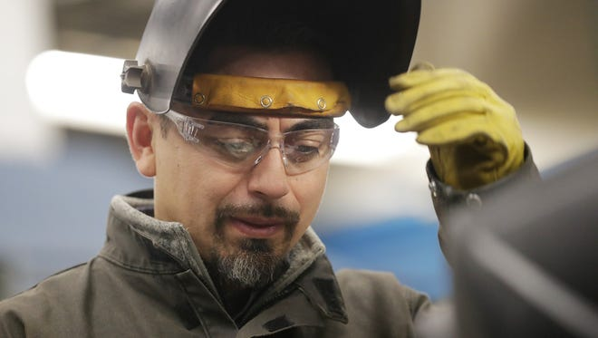 Welding instructor Luis Bolanos works with students in a welding lab at Northeast Wisconsin Technical College. Bolanos moved to Green Bay from Mexico when he was 18.