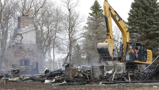 Smoldering rubble is cleared from the scene of a fire at 3302 Breezewood Lane in Clayton on Tuesday. The remains of two people were found inside.