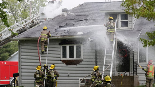 Firefighters try to extinguish a fire located at 524 East Quincy St. Monday in New London.