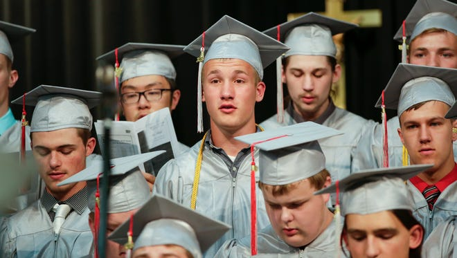 """Graduates sing their senior anthem, """"Be Still"""" by Mary McDonald, during the Manitowoc Lutheran graduation ceremony at Manitowoc Lutheran High School Saturday, May 26, 2018, in Manitowoc, Wis."""
