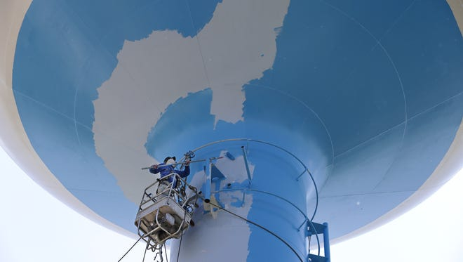 Carlos Martinez, an employee with V & T Painting out of Farmington Hills, Michigan, paints the underside of a water tower in Menasha.