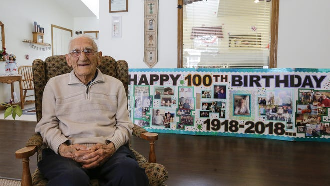 Bill Ahearn poses for a portrait on his 100th birthday at Wisteria Haus June 12 in Two Rivers.