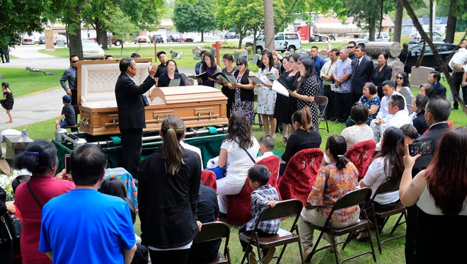 Mourners of Hmong veteran Pa Xang Her of Green Bay gather for his burial with military honors at the Fort Howard Memorial Park cemetery on Monday, July 9, 2018 in Green Bay, Wis.