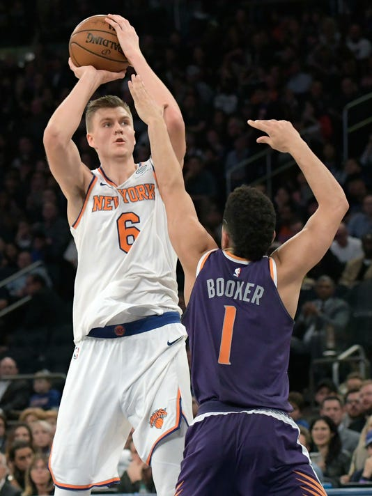 New York Knicks forward Kristaps Porzingis (6) shoots over Phoenix Suns guard Devin Booker (1) during the second quarter of an NBA basketball game Friday, Nov. 3, 2017, at Madison Square Garden in New York. (AP Photo/Bill Kostroun)