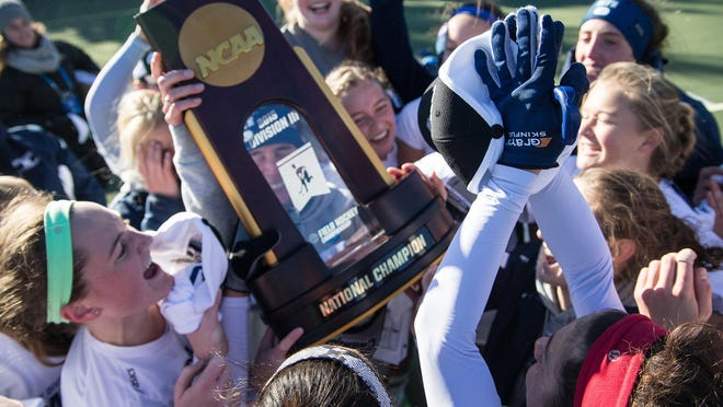 The Middlebury College field hockey celebrates after beating Bowdoin to win the NCAA Championship.