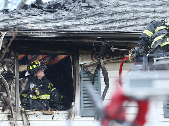 Parsippany firefighters vent the eaves of a family