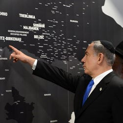 Israeli Prime Minister Benjamin Netanyahu points at an exhibit in 2013 showing where Jews were killed in the Holocaust.
