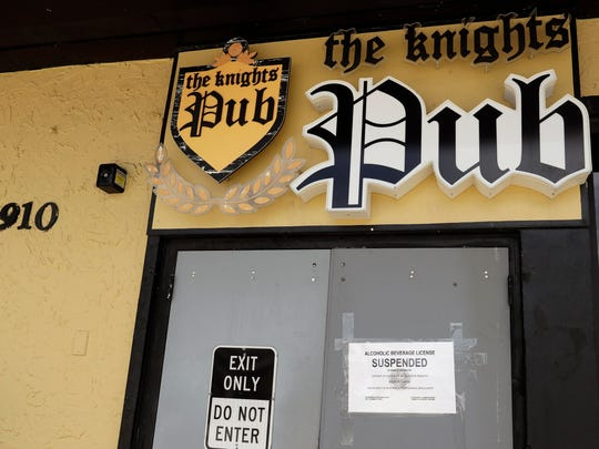 A sigh indicating the suspension of an alcohol license is seen on an exit door at The Knight's Pub in Orlando, Fla. Dozens of workers and patrons have tested positive for the new coronavirus at the establishment, leading to the suspension of its alcohol license.