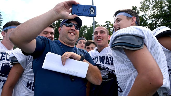 Medway football coach Anthony Mazzola shows his players a video of his son playing youth football before practice last year. Mazzola is unsure if he'll be able to do a similar thing when it comes to football this fall.