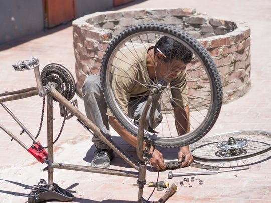 """Sergio Guzman Vazquez, 51,repairs on old bicycle wheel in the courtyard of La Posada del Migrante, a shelter for deported migrants in Mexicali. He was deported in May 2016 from Los Angeles after he was charged with a felony DUI. He said he does not intend to try to cross back into the United States with President Donald Trump in the White House. """"I am nervous about crossing,"""" he said. """"I am afraid I could get shot."""""""