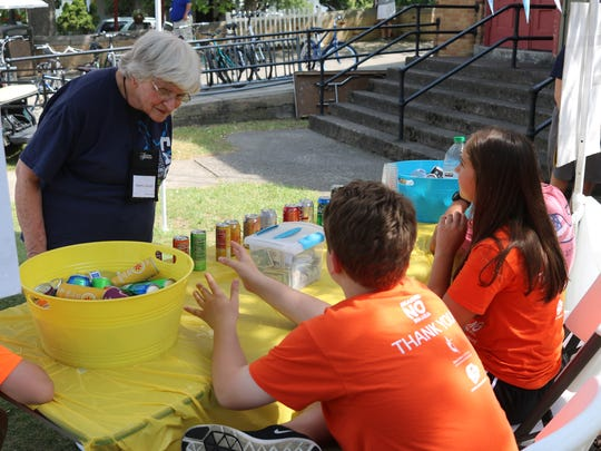 Martha Wason, left, buys a refreshment from the charity lemonade stand started by local teens Molly McNamara and Logan Martens, which has raised more than $80,000 to prevent malaria in Africa.