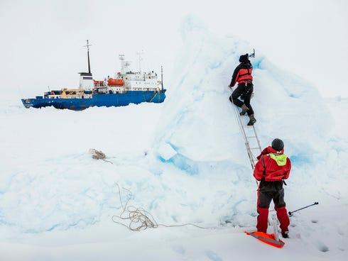 In this Dec. 31, 2013, image provided by Australasian Antarctic Expedition/Footloose Fotography, Ben Maddison and Ben Fisk from the Russian ship MV Akademik Shokalskiy work to place a wind indicator atop an ice feature near the trapped ship 1,500 nau