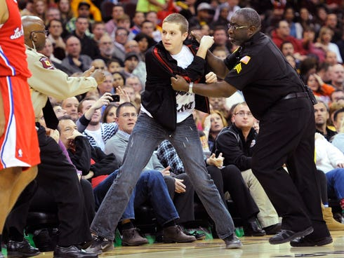 Dec 7, 2013; Cleveland, OH, USA; Security grabs a fan who walked on to the court in the second quarter during a game between the Cleveland Cavaliers and the Los Angeles Clippers at Quicken Loans Arena. Mandatory Credit: David Richard-USA TODAY Sports