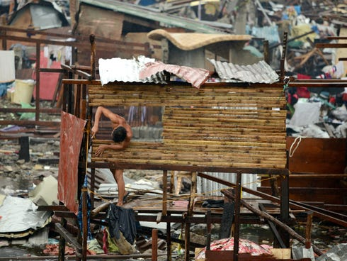 A man reconstructs his destroyed house in Tacloban, on the eastern island of Leyte, on Nov. 12, 2013.