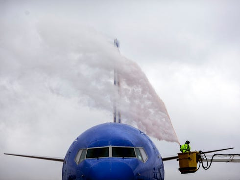 A worker from Wilson Air Center de-ices a Southwest Airlines plane at the Memphis International Airport on Dec. 6, 2013.