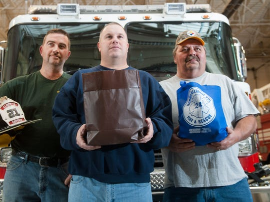 (From l-r); Washington Township firefighter Eric Fitzpatrick, Washington Township firefighter Scott Sheldrick, and Landisville firefighter engineer Dave Bauer Jr. hold items donated by area fire departments that the firefighters will give to 7-year-old  Aiden Riebel of Washington Township,  who is fighting acute myeloid leukemia and was sworn in as Washington Township's first honorary firefighter a year ago, as the firefighters stand in the Grenloch Station 10-1 in Washington Township.
