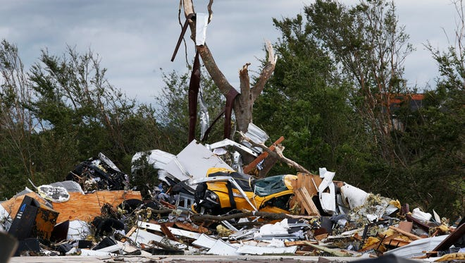 Cars and damaged material is seen piled up at a local car dealership that was destroyed when a large tornado hit the area near Canton, Texas, on April 29, 2017.